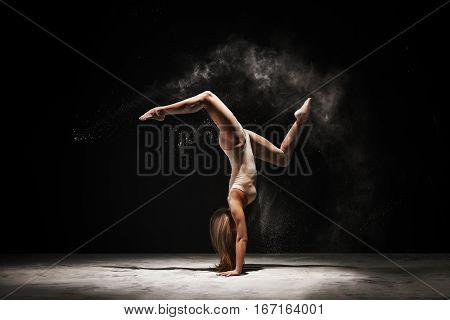 Slender woman dancing in cloud of white dust doing handstand studio shot