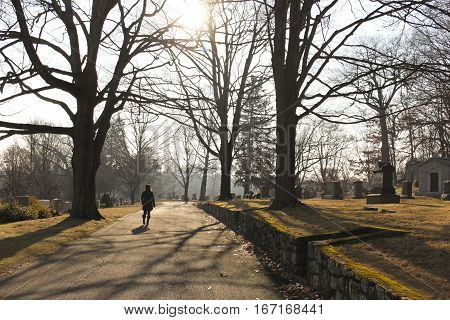 woman silhouetted by sunlight while walking along a path in a cemetery