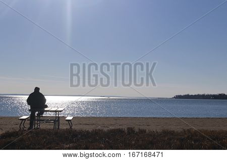 Man silhouetted on a bench looking out to sea
