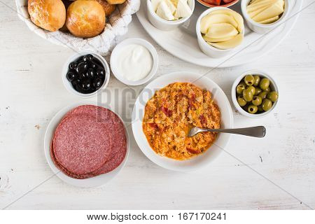 Traditional Turkish breakfast top view: cooked egg menemen pogaca pasties vegetables cheeses olives and halal turkey salami selective focus