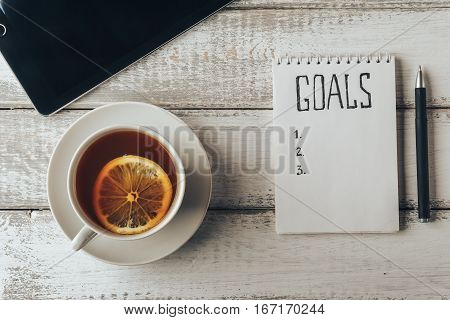 Goals concept. Notebook with goals list, tablet cup of tea on wooden table. Motivation and strategy concept. Top view. Retro toned image.