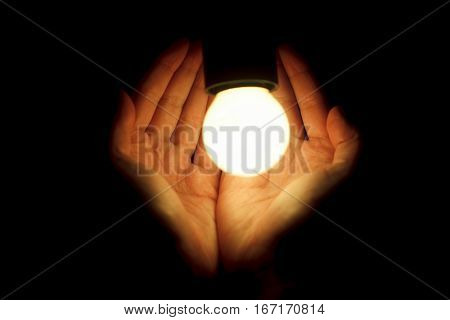 Hands Of Human Holding Illuminated Led Bulb On Black Background. Eco Safe The Planet Concept. New Id