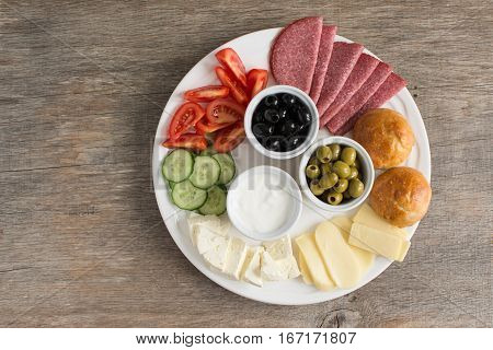 Traditional Turkish breakfast platter on the grey wooden table top view: pogaca pasties vegetables cheeses olives and halal turkey salami selective focus; copy space for text