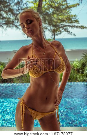 Sensual blond woman wearing crochet bikini standing near the swimming pool at tropical resort hotel over sea and sky background