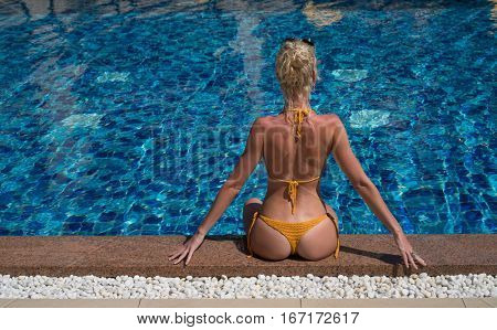 Back view of sensual blond woman wearing crochet bikini sitting at the edge of swimming pool at tropical resort hotel