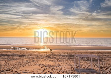 A few people walking in the beach during the sunset in a cold winter evening.