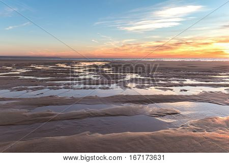 A beautiful sunset in the fine sand beach during a winter evening.