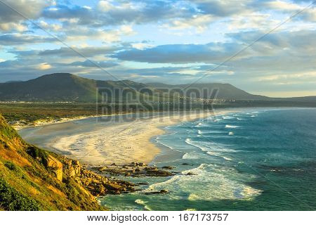 Scenic aerial view of Noordhoek Beach, Table Mountain National Park, South Africa at sunset. Noordhoek Beach, 8 km of sandy beach from Chapmans Peak Drive to Kommetjie and Slangkop Lighthouse.