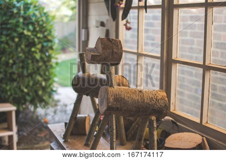 Dark toned photography: making wooden reindeers from the logs in the shed selective focus