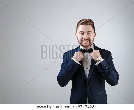 Handsome smiling man in tuxedo and bow tie looking at camera. Fashionable and festive clothing. emcee on grey background
