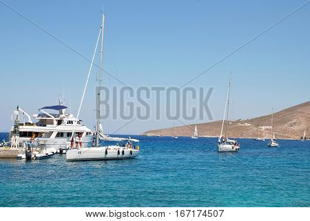 TILOS, GREECE - JULY 19, 2016: Competitors in the annual Rhodes Cup Regatta enter Livadia harbour on the Greek island of Tilos. The international yacht race is in its twentieth year.