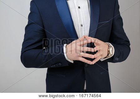 hands of a young successful businessman in a tuxedo and a gray background. the groom at the wedding