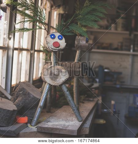 Dark toned photo: making wooden reindeer from the logs in the shed; unfinished wooden deers selective focus