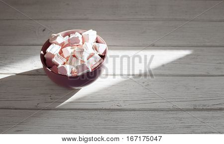 Marshmellow in a bowl on a wooden background. The concept of food.