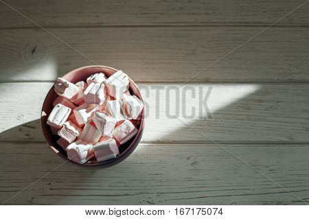 Marshmellow in purple bowl on a wooden background. Top view. The concept of food.