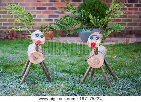 Two wooden handmade reindeer on the grass in winter selective focus on the reindeer on the right