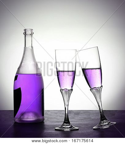 Bottle and moving glasses with lilac liquid