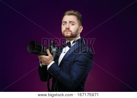 young successful professional photographer in tuxedo use DSLR digital camera on dark background