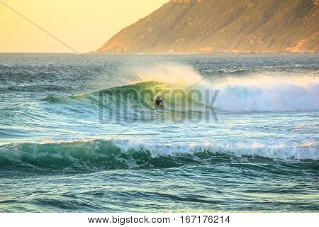 Noordhoek Beach at sunset. Surfing in Cape Town, South Africa. Surfer tries to take a big wave. Atlantic coast in Table Mountain National Park. Extreme sports leisure concept.