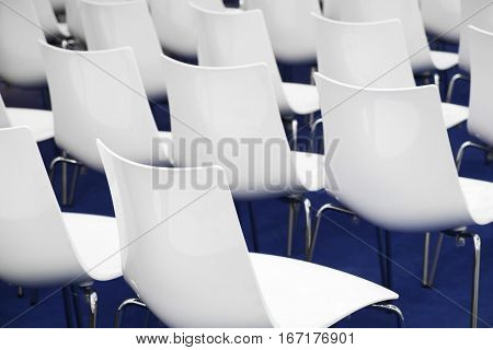Conference chairs in business room rows of white plastic comfortable seats in empty corporate presentation meeting office detail selective focus blue floor