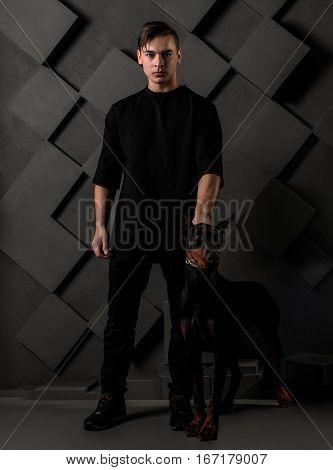 muscular man standing with black doberman dog on black grid background