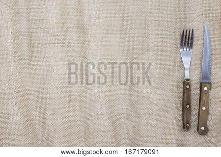 Canvas tablecloth and fork and steak knife. Is used to create a menu for a Steakhouse. The background for the menu.