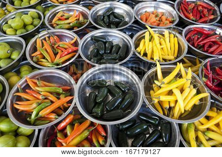 Hot peppers different varieties is on the plates on the counter market. Chile pepper, Cayenne pepper, Pungent bouquet of pepper, Chinese pepper. Great photo for the sellers of vegetables