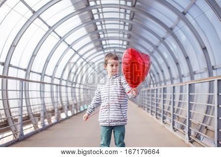 kid with a red balloon as an heart. dreamy boy with red heart in hands. the concept of Valentine's day