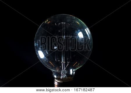 Antique unlit light bulb isolated on black background