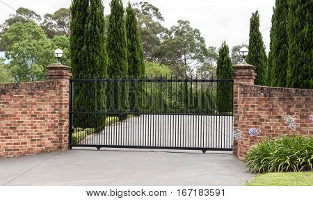Black wrought iron metal driveway entrance gates set in brick fence