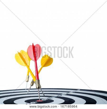 Close up shot red dart arrow on center of dartboard and yellow arrow not hit the target with copyspace metaphor to target success Isolated on white background with clipping path selective focus on red arrow