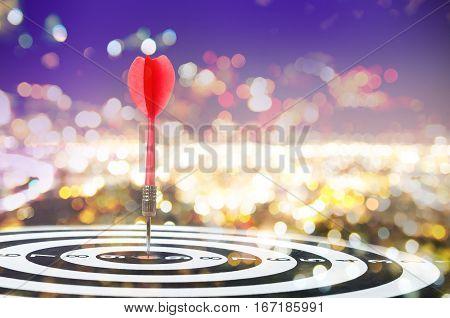 Close up shot red dart arrow on center of dartboard on bokeh blur background metaphor to target success winner concept