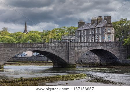 Wick Scotland - June 4 2012: Historic bow gray stone bridge over shallow Wick River downtown under rainy cloudy skies. Green foliage of trees and gray stone hotel in background. Look through the bows.