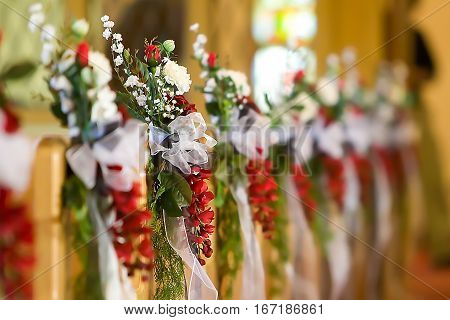 A wedding flower arrangement at the end of pews