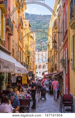 Monaco, Monte Carlo - September 16, 2016: Rock of Monaco.  Rue Comte Félix Gastaldi the street with restaurants and cafes with people ant tourists. The street leads to the palace of Monaco.