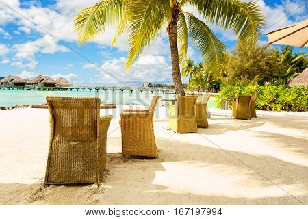 Two chairs and on a sand beach with a view on the lagoon and Mount Otemanu on the tropical island of Bora Bora near Tahiti in French Polynesia.