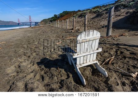 A white chair sits on the beach next to a fence at Baker Beach and the Golden Gate Bridge