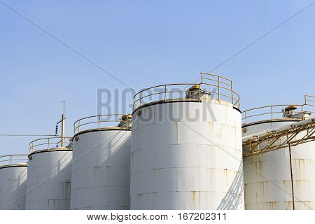 The old big industrial container tank for keep the chemical liquid with the blue sky