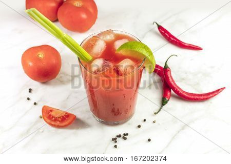 Bloody Mary cocktail on a white marble texture, with red hot chili peppers, slices of lime, a celery stick, a piece of tomato and copy space