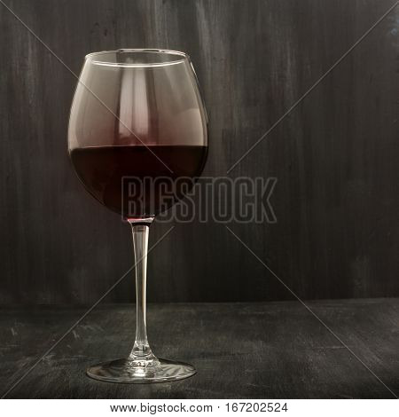 A square photo of a red wine glass on a very dark background texture, with copy space. Low-key image, toned