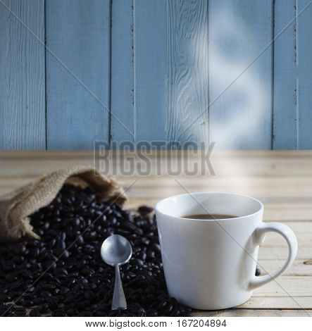 cup of coffee and seed of coffee with smoke on wood background