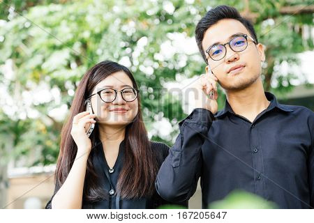 Businesman And Woman Use Cellphone For Business Talking In Park