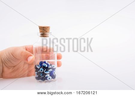 Little  Glass Bottle With Blue Evil Eye Beads In Hand