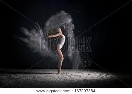 Slender woman dancing in cloud of white dust studio portrait