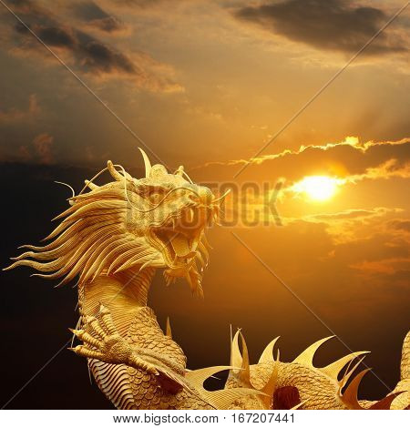 Golden chinese dragon on dramatic sky at sunset.