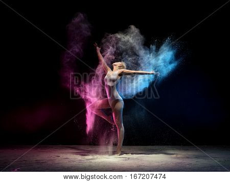 Woman in beige body posing in cloud of pink and blue dust streching gracefully up