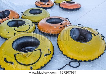 Yellow and orange large inflatable tubes used for snow tubing on downhill slopes