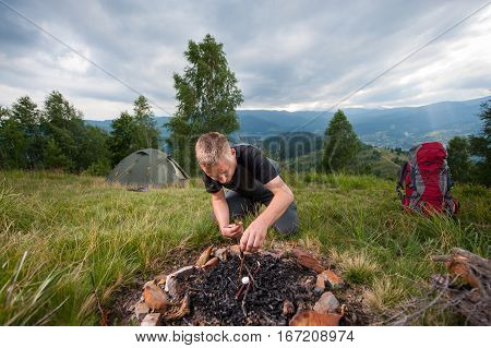 Young Male Hiker Kindling Firewood On The Hill With Tent