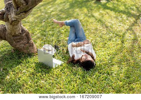 woman relaxing and listen music at park