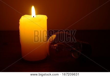 Burning candle and lamp on desktop in darkness (no electricity)
